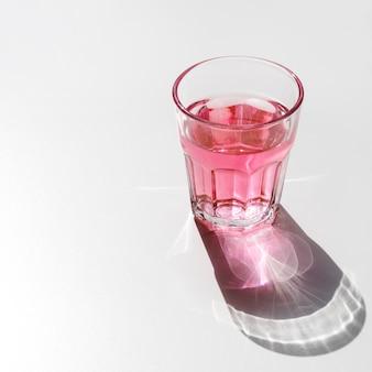 Vidro líquido vermelho com sombra escura de brilho no fundo branco