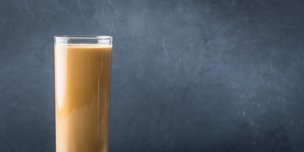 Vidro longo com café e creme no fundo escuro. bandeira