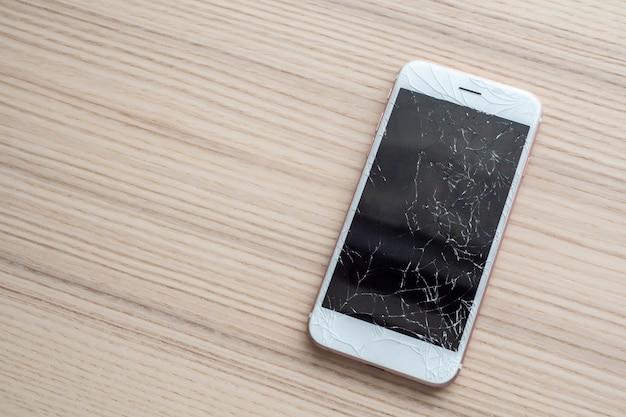 Vidro quebrado da tela do celular na mesa de madeira