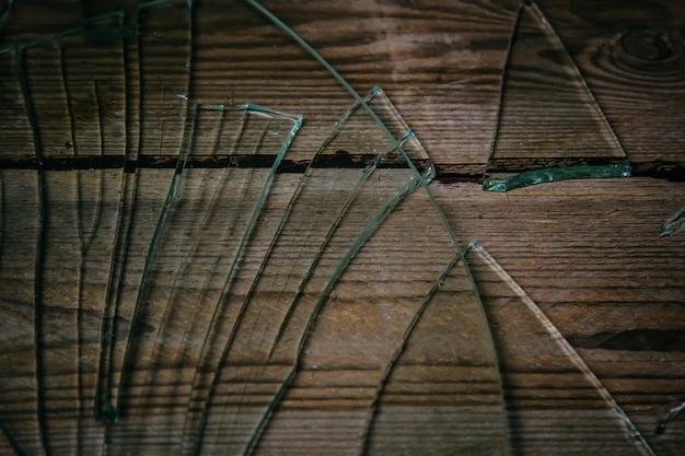 Vidro quebrado em um assoalho de madeira velho, conceito de violência.