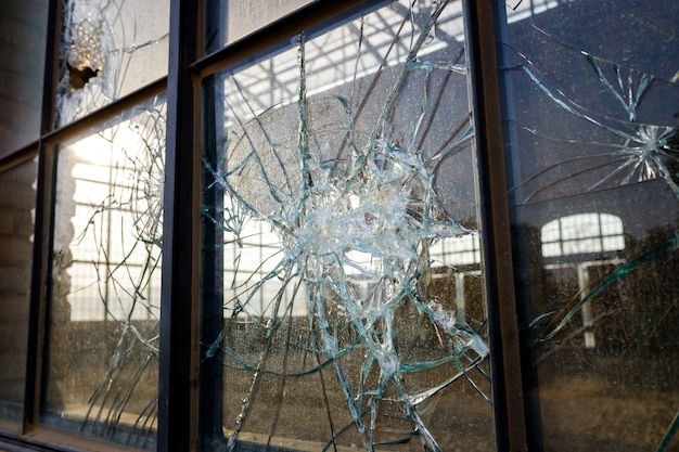 Vidro quebrado grosso de uma janela em uma zona industrial abandonada.