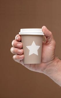 Vidro térmico com estrela e tampa na mão fundo marrom