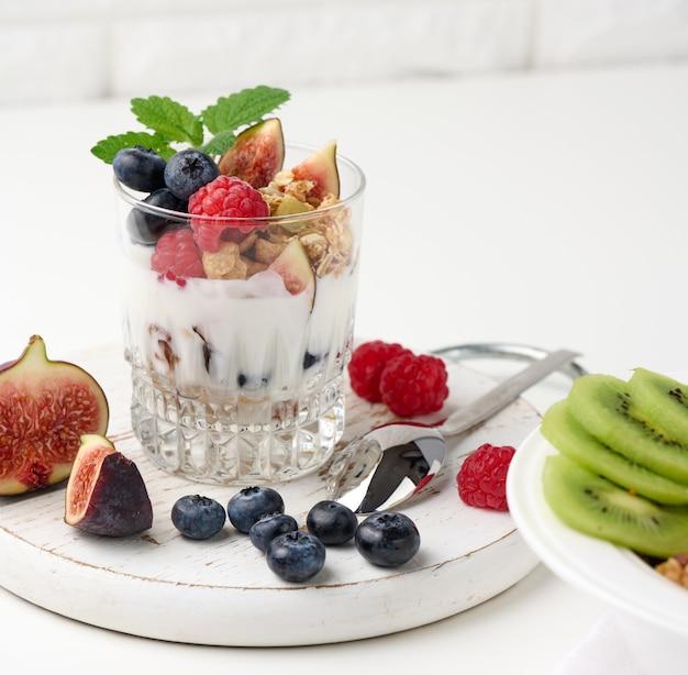 Vidro transparente com granola derramada com iogurte, em cima de framboesas maduras, mirtilos e figos em uma mesa branca. café da manhã saudável
