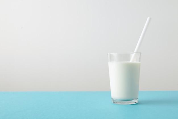 Vidro transparente com leite orgânico fresco e canudo branco dentro isolado na mesa azul pastel