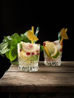 Vidro transparente com limonada e pedaços de gelo, frutas vermelhas