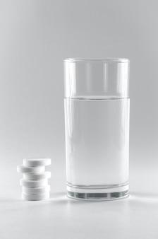 Vidro transparente de água e comprimidos efervescentes solúveis isolados no branco