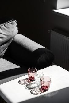 Vidro vermelho cristal na mesa branca. sombras duras à luz do sol.