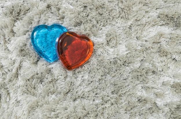 Vidro vermelho e azul em forma de coração no tapete cinza