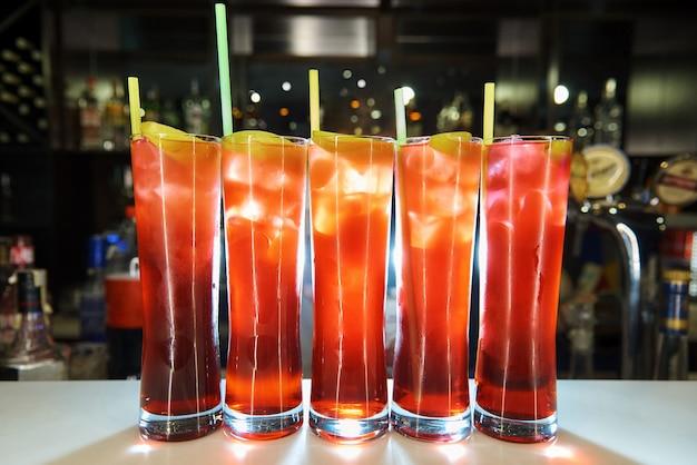 Vidros altos com os cocktail frios brilhantes no fundo de uma barra borrada com um bokeh.
