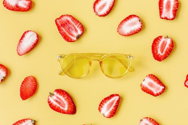 Vidros amarelos sobre um fundo colorido rodeado por morangos.