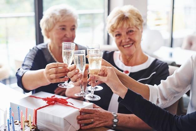 Vidros batendo. mulher sênior com família e amigos comemorando um aniversário dentro de casa.