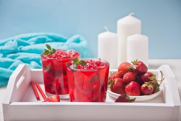 Vidros com chá gelado doce da morango caseiro fresca ou cocktail, limonada com hortelã. bebida e placa frias de refrescamento com a morango na bandeja branca de madeira.