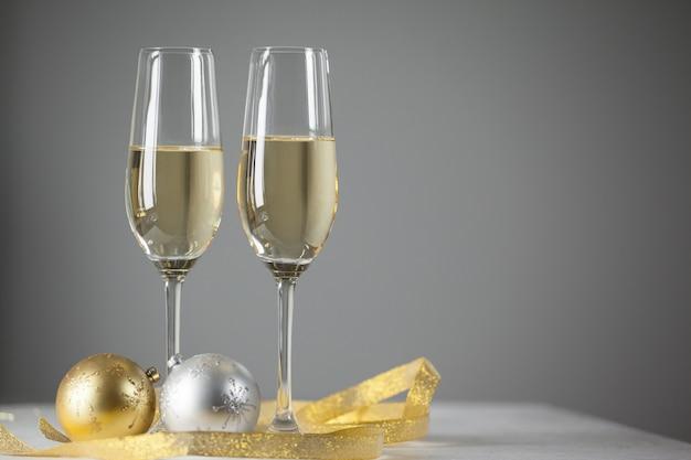 Vidros com champanhe e presentes de fundo
