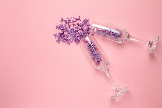 Vidros de champagne com as flores lilás no estilo mínimo do papel cor-de-rosa da cor. férias de verâo.