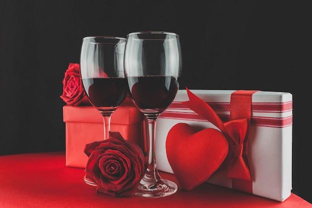 Vidros de vinho com presentes e um coração