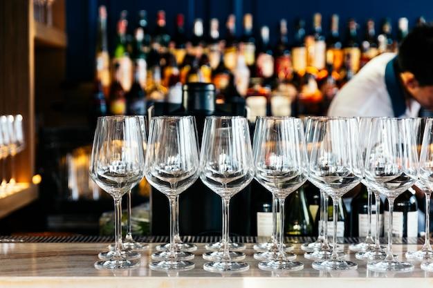 Vidros de vinho vazios na tabela contrária com vinho, licor e espírito do borrão no fundo.