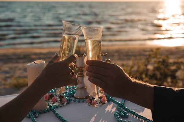 Vidros do champanhe no beira-mar - decoração da cerimônia de casamento.