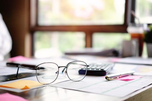 Vidros do equipamento do negócio, papel financeiro dos dados e calculadora na tabela do escritório.