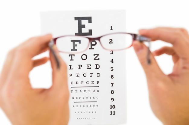 Vidros mantidos para ler o exame de olho