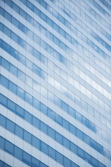 Vidros que constroem o fundo da textura com refletem do céu azul e das nuvens no dia claro.