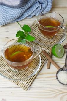 Vidros quentes do chá do limão com a vara de canela na esteira de bambu e no ofício.