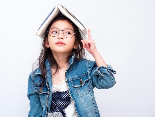 Vidros vestindo da menina bonito pequena asiática com o livro na cabeça e no dedo apontando acima.