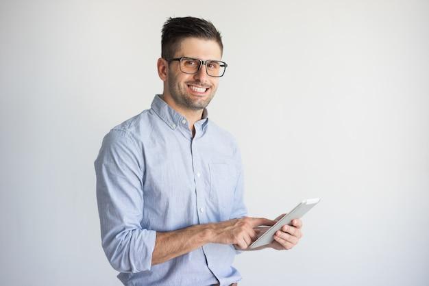 Vidros vestindo de sorriso do homem de negócios novo usando a tabuleta digital.