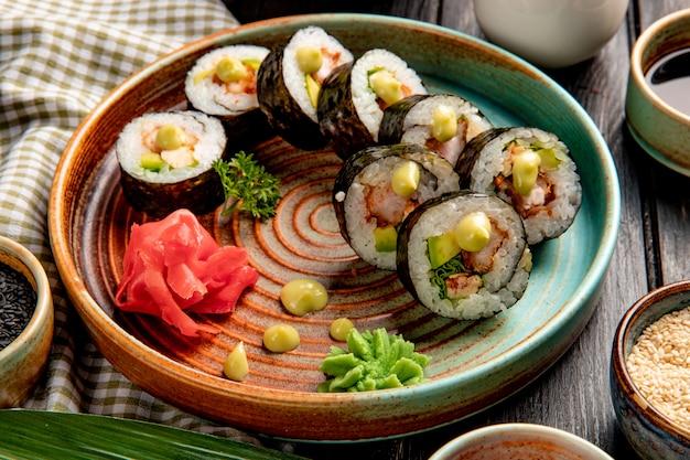 Vie lateral de rolos de sushi com camarão tempura abacate e creme de queijo em um prato com gengibre e wasabi