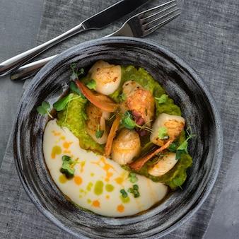 Vieiras com ervilhas e molho de beurre blanc. prato de argila cinza, colher, garfo numa toalha de mesa cinza
