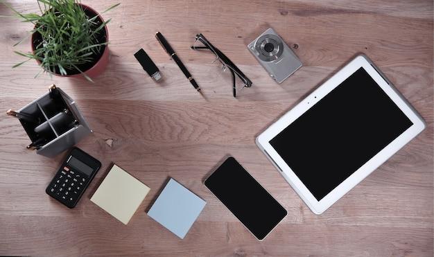 View.desktop superior com fundo de tablet, calculadora e material de escritório.