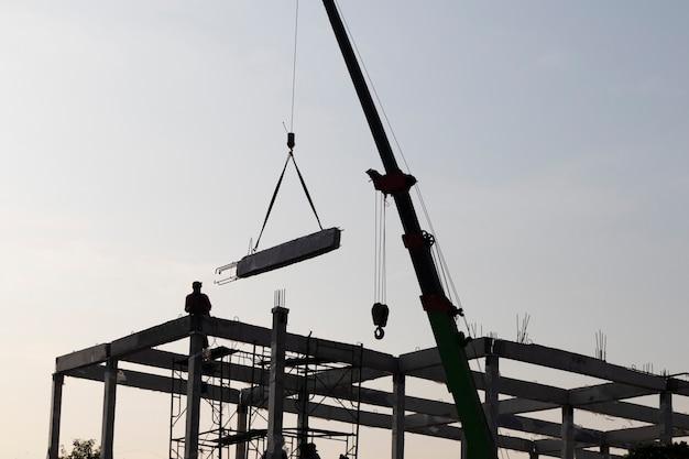 Viga pré-moldada de concreto instalada no canteiro de obras por guindaste móvel; fundo de engenharia civil