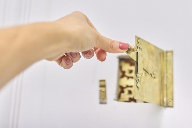 Vigia de metal dourado antigo vintage na porta da frente, trava de abertura de mão de mulher