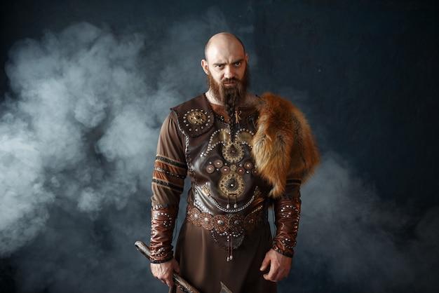 Viking barbudo com machado vestido com roupas nórdicas tradicionais