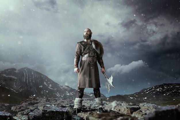 Viking com machado vestido com roupas nórdicas tradicionais, de pé nas montanhas rochosas. antigo guerreiro escandinavo