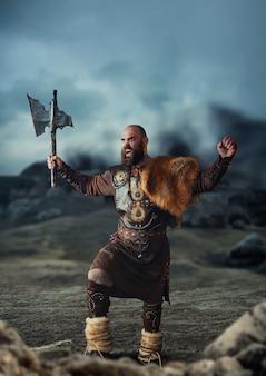 Viking com machado vestido com roupas nórdicas tradicionais de pé nas montanhas rochosas e levantando as mãos