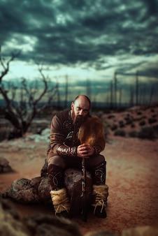 Viking com machado vestido com roupas nórdicas tradicionais sentado em uma pedra em terreno baldio, batalha em montanhas rochosas. antigo guerreiro escandinavo