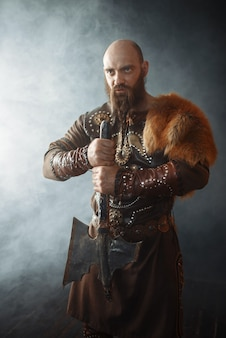 Viking com machado vestido com roupas tradicionais, imagem bárbara nórdica. guerreiro antigo em fumaça