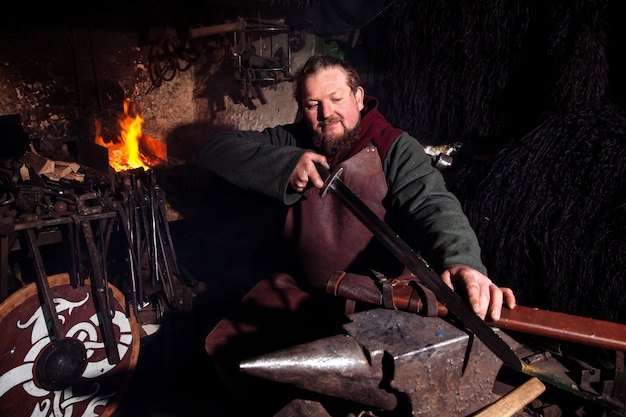 Viking forja armas e espadas na ferraria. um homem com roupas de guerreiro está na ferraria.