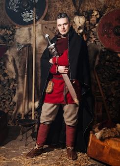 Viking posando contra o antigo interior dos vikings. Foto Premium