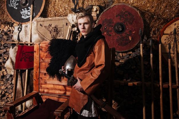 Viking posando contra o antigo interior dos vikings.