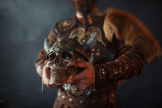 Viking segurando crânio humano em capacete