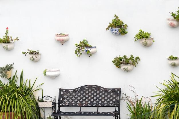 Vila branca típica com os vasos de flores em fachadas na espanha. potes de cerâmica diferentes com flores penduradas em uma parede branca