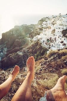 Vila de oia, vista de duas pessoas com pernas visíveis na foto.