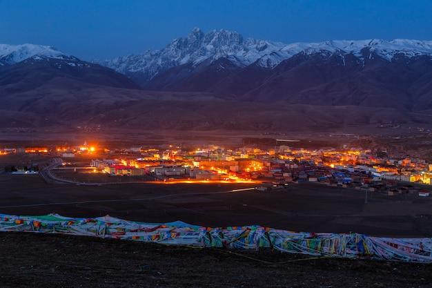 Vila inclue a montanha um marco famoso em ganzi na noite, sichuan, china.