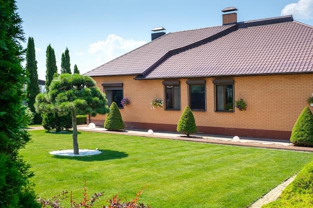 Villa de estilo europeu com jardim nas traseiras com árvores bem aparadas e arbustos perto da casa. projeto paisagístico. foto de alta qualidade