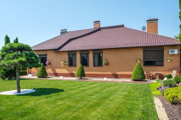 Villa e jardim de estilo europeu com arbustos e árvores bem aparados