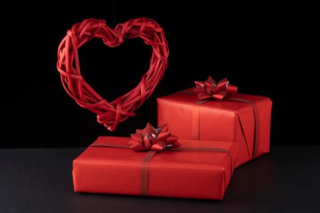 Vime levitando coração vermelho e caixas de presente na superfície preta.