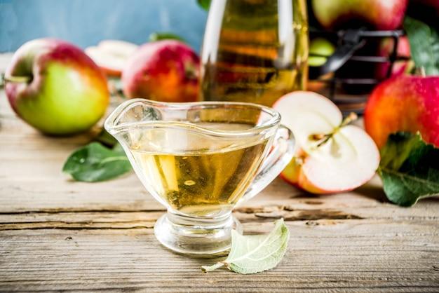 Vinagre de maçã caseiro com maçãs frescas om fundo rústico de madeira