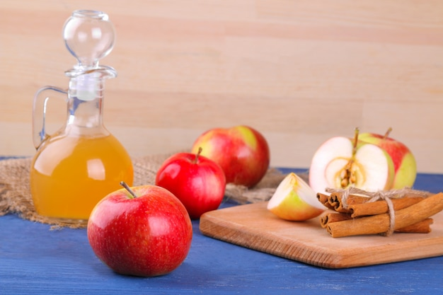Vinagre de maçã com maçãs frescas maduras em um fundo de madeira
