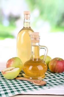 Vinagre de maçã em garrafas de vidro e maçãs frescas maduras, na mesa de madeira, no fundo da natureza